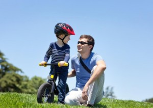 happy smiling father with his son on a balance bike
